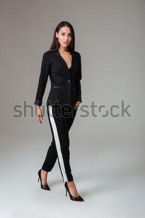 Young brunette woman in black suit walking Stock photo © deandrobot