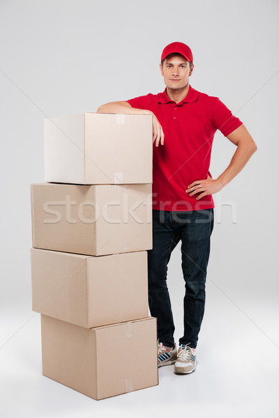 Smiling courier in red shirt leaning on stack of box Stock photo © deandrobot