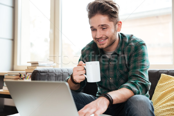 Happy man looking at laptop on sofa Stock photo © deandrobot