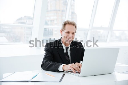 Elderly business man with laptop and documents Stock photo © deandrobot