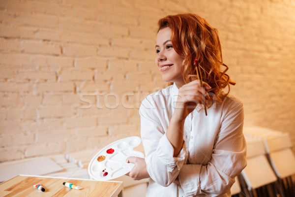 Cheerful redhead woman painter with oil paints and palette Stock photo © deandrobot