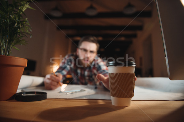 Tired bearded man trying to reach coffee cup while working Stock photo © deandrobot