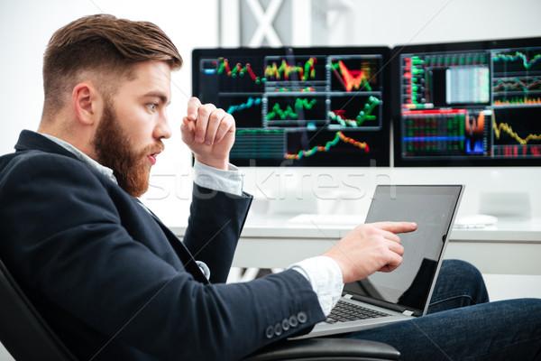 Maravilhado empresário usando laptop indicação escritório barbudo Foto stock © deandrobot