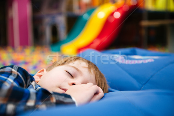 Tired exhausted little boy sleeping at indoor amusement park Stock photo © deandrobot