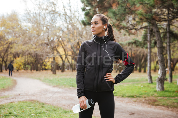 Female young runner in warm clothes looking aside Stock photo © deandrobot