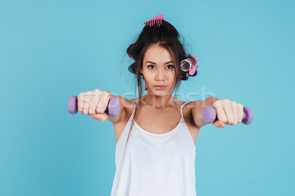 Portrait of a serious young woman with curlers doing exercises Stock photo © deandrobot