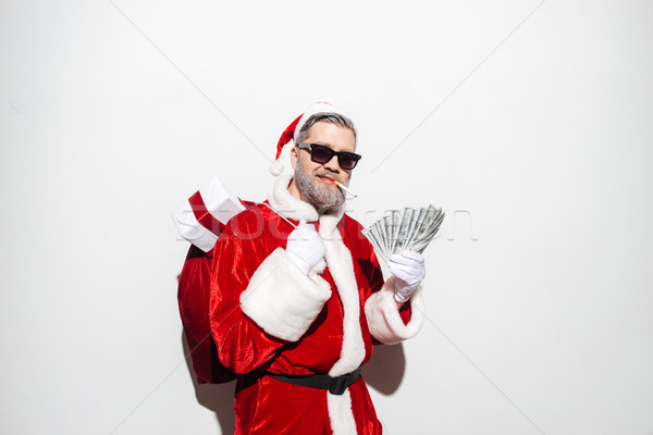 Man santa claus in sunglasses with present sack and money Stock photo © deandrobot