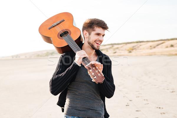 Casual hombre caminando playa guitarra Foto stock © deandrobot