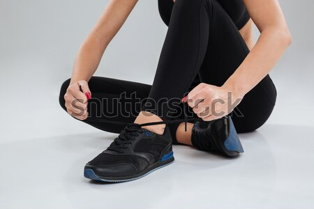 Cropped image of a sports female sitting and tying shoelace Stock photo © deandrobot
