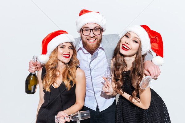 Happy bearded man with two women in santa claus hats Stock photo © deandrobot