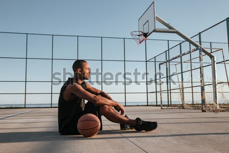 Afro american sports man lying on the playground with basketball Stock photo © deandrobot
