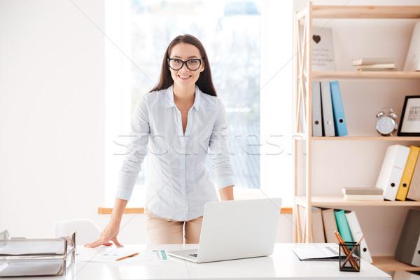 Jovem alegre empresária em pé mesa de escritório olhando Foto stock © deandrobot