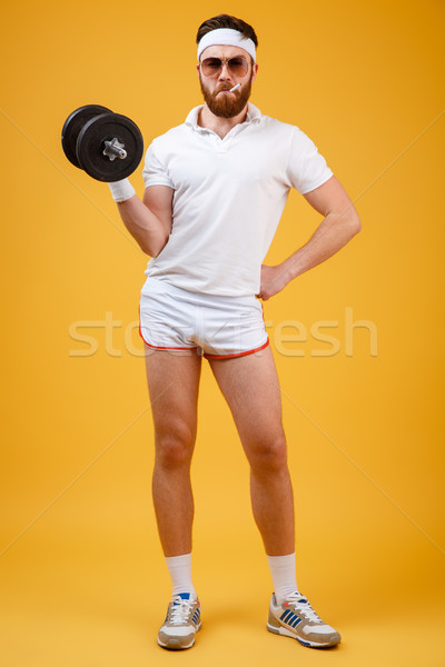 Vertical image of sportsman with cigarette holding dumbbell Stock photo © deandrobot