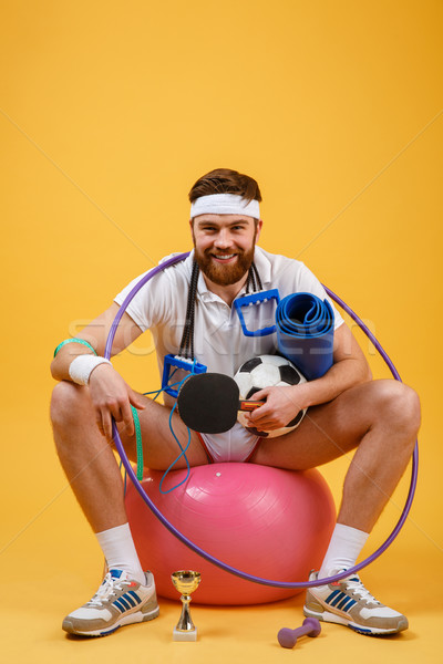 Happy cheerful fitness man sitting on a sports ball Stock photo © deandrobot