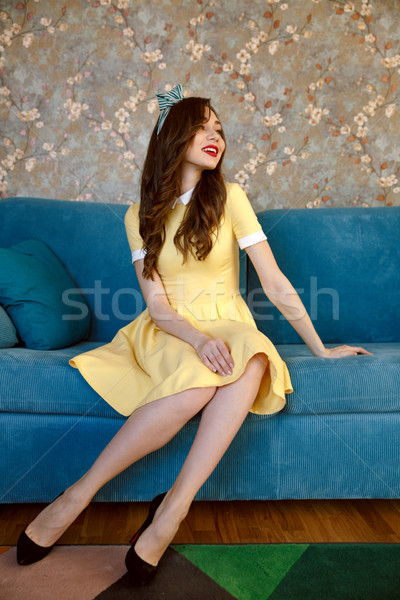 Happy young pin-up lady sitting on sofa at home. Stock photo © deandrobot