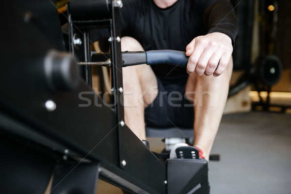 Cropped image of Muscular man using rowing machine Stock photo © deandrobot