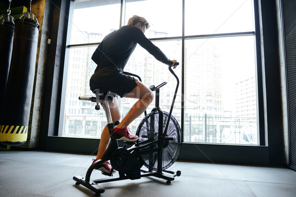 Back view of Muscular man using spinning bicycle Stock photo © deandrobot