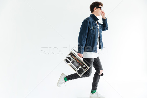 Attractive young man holding boombox. Looking aside. Stock photo © deandrobot
