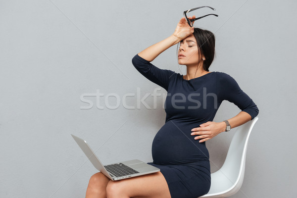 Bored pregnant business woman sitting over grey background Stock photo © deandrobot