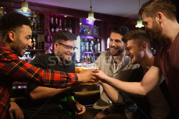 Happy male friends drinking beer and clinking glasses at bar Stock photo © deandrobot