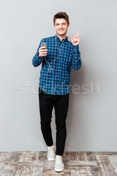 Full-length shot of man listening music in headphones Stock photo © deandrobot
