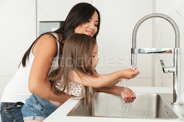 Young asian mother helping her daughter to wash hands Stock photo © deandrobot