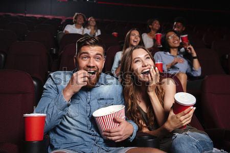 Loving couple sitting in cinema watch film Stock photo © deandrobot