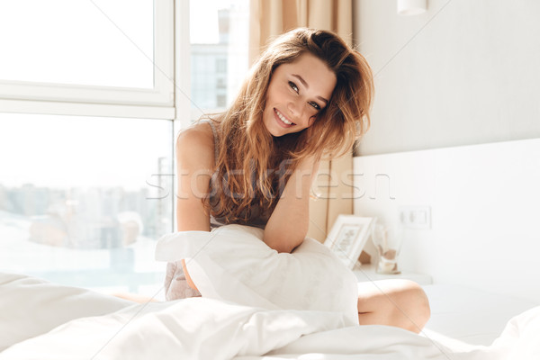 Positive woman with pillow sitting in bed Stock photo © deandrobot