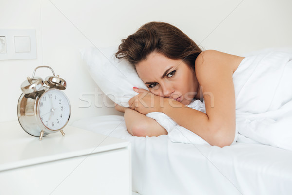 Angry pretty woman laying in bed in the morning Stock photo © deandrobot