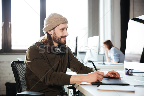 Handsome man work in office using computer. Stock photo © deandrobot