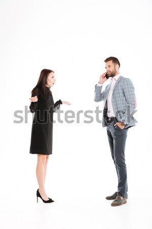 Offended young loving couple standing isolated Stock photo © deandrobot