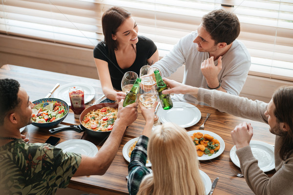 Group of people clinking glasses and bottles at the table Stock photo © deandrobot