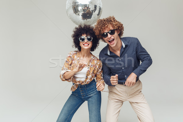 Emotional smiling retro loving couple dancing near disco ball. Stock photo © deandrobot