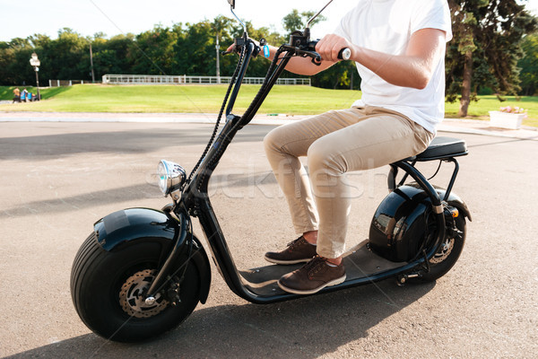 Cropped side view of young man rides on modern motorbike Stock photo © deandrobot