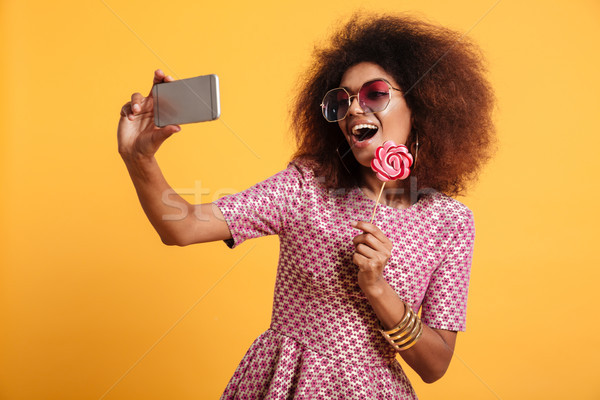 Portrait of a pretty laughing afro american woman Stock photo © deandrobot