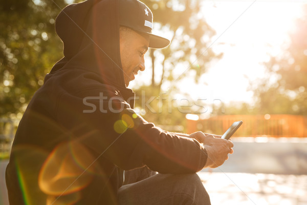 African young man surfing the web by using a smartphone Stock photo © deandrobot