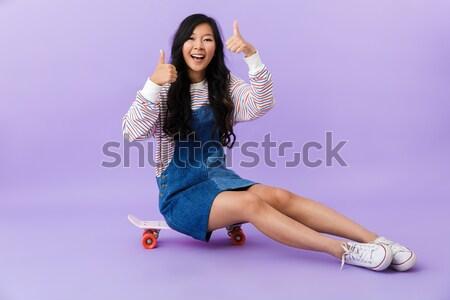 Beatiful woman sitting on skateboard on floor isolated Stock photo © deandrobot