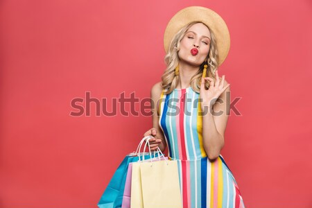 Cheerful woman talking on smartphone and holding bags isolated Stock photo © deandrobot