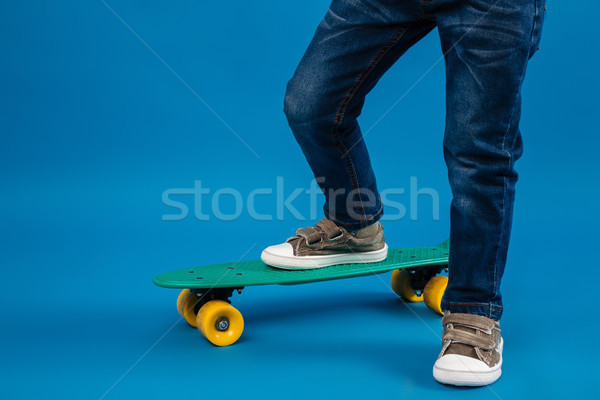 Cropped image of young boy comes on skateboard Stock photo © deandrobot