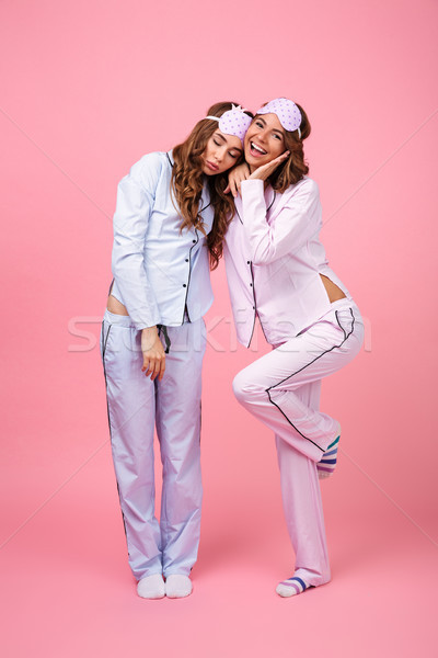 Woman in pajama looking camera while her friend sleeping Stock photo © deandrobot