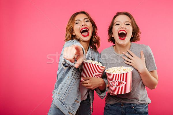 Alegre risonho mulheres amigos alimentação pipoca Foto stock © deandrobot