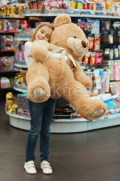 Delighted little girl holding big teddy bear Stock photo © deandrobot