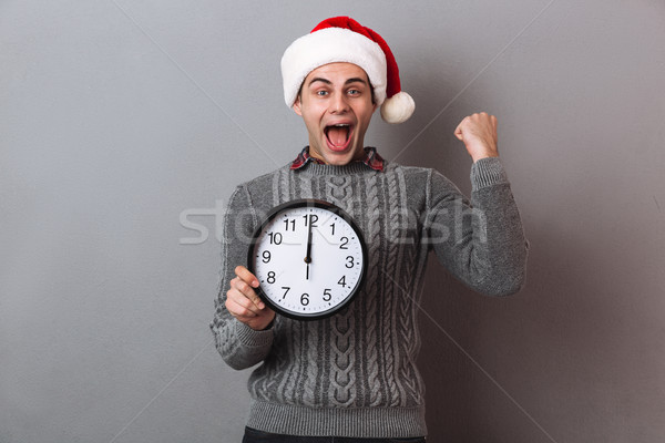 Happy screaming man in sweater and christmas hat holding clock Stock photo © deandrobot