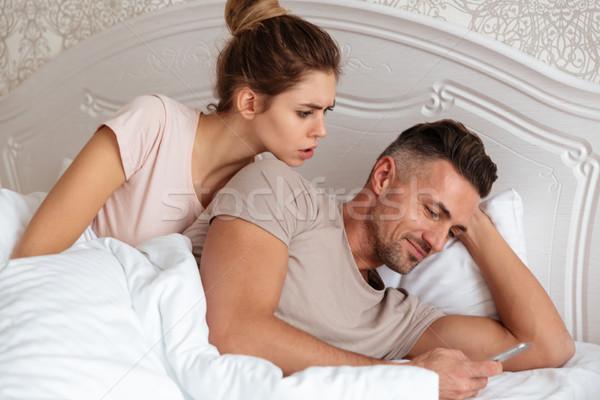 пару вместе кровать человека смартфон концентрированный Сток-фото © deandrobot