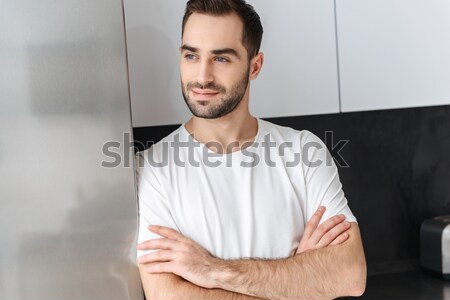 Handsome young serious man with arms crossed. Looking camera. Stock photo © deandrobot