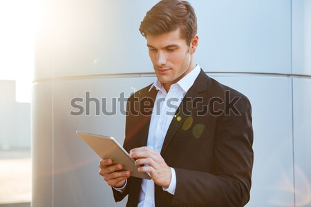 Handsome young man using laptop computer. Stock photo © deandrobot