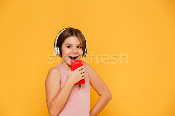 Happy girl looking aside while using heeadphones and singing in smartphone isolated Stock photo © deandrobot