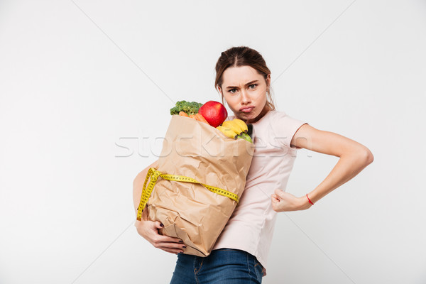 Portrait of a serious girl holding bag with groceries Stock photo © deandrobot