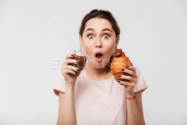 Portrait of a cheery pretty girl eating croissant Stock photo © deandrobot