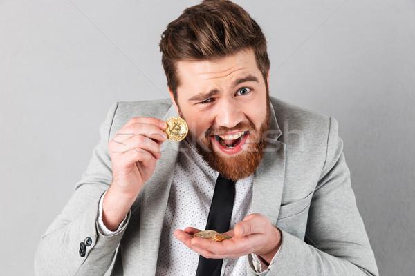 Portrait of a confident businessman showing golden bitcoins Stock photo © deandrobot